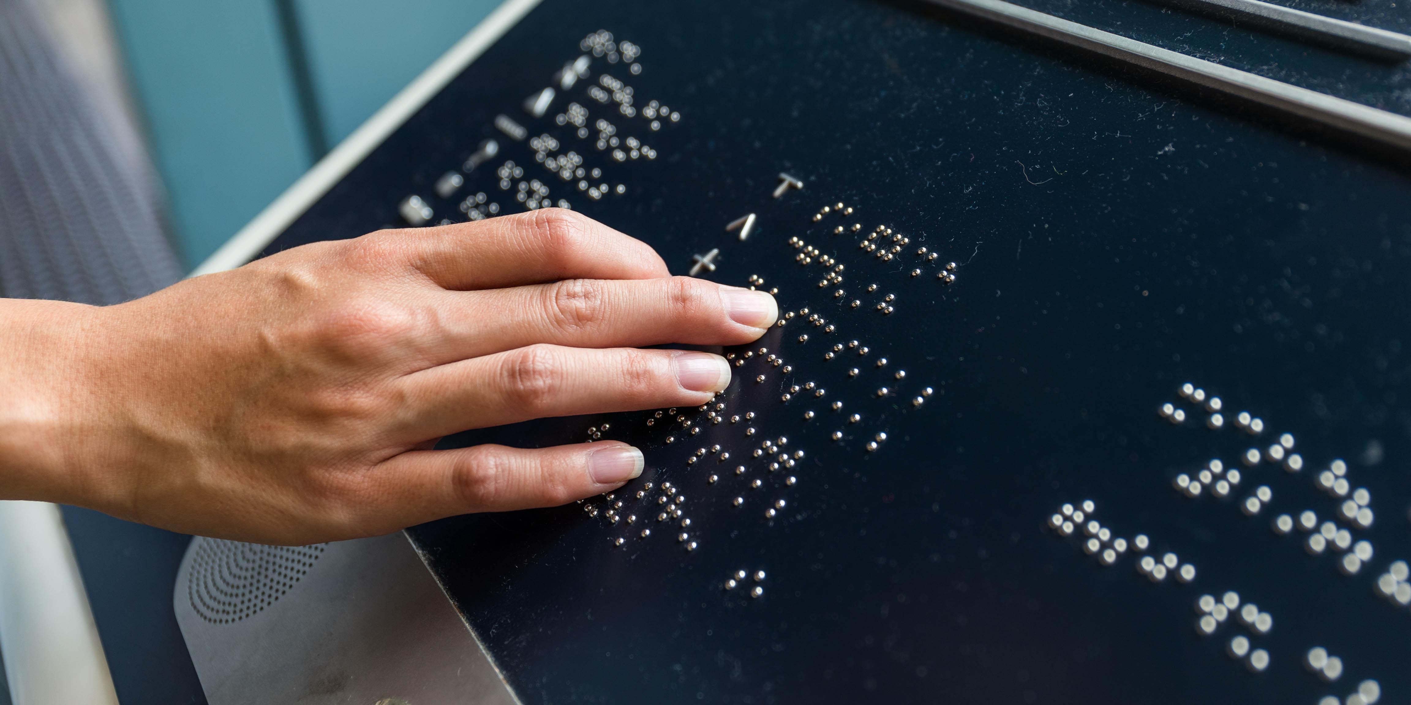 Doigts sur caractères braille