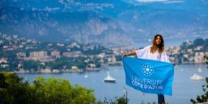 Jeaune femme tenant le drapeau UCA devant un paysage de mer et montagne